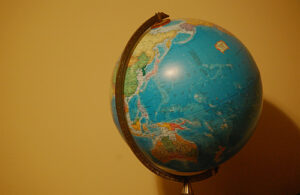 A globe stands in front of a bright yellow wall. Australia and parts of Asia can be seen on the globe.