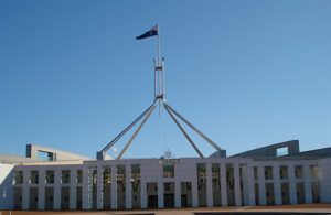 Australia's parliament house, including the flagpole, against a background of clear blue sky.