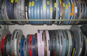 A number of movie canisters in a range of colours including silver, blue, red, pink and green. Many of them have been labeled in handwriting or with Dymo labeling tape. The canisters are housed on a rack.