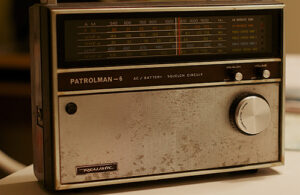 A silver Realistic analogue radio sits on a table. It features a large tuner knob, volume knob and the text, 'Patrolman–6'.