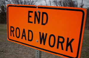 An orange road sign that reads, 'End Road Work'.