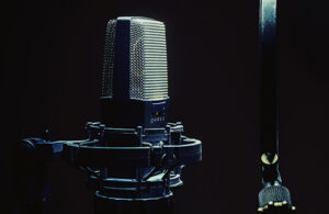 A microphone is suspended in a microphone boom arm against a dark background.