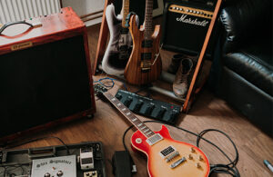 A guitar lies on the floor of a studio, with two other guitars in a guitar stand and two amps in the background.