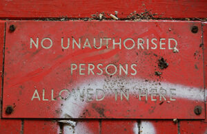 A red sign on a painted red wall that reads, 'No unauthorised persons allowed in here' in white text styled in all capital letters.