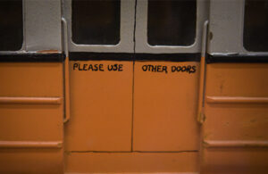 Orange train doors with 'Please use other doors' painted by hand on the doors.