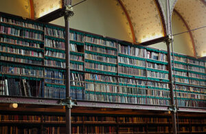 An historic library with full bookshelves with hundreds of books.