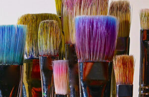 Paint brushes with blue, pink, purple and yellow in the bristles.