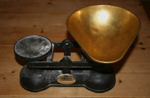 A set of kitchen scales on top of a wooden bench.