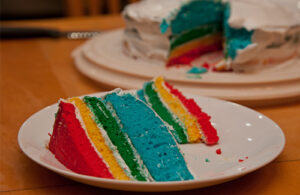 A slice of cake on a white plate has four layer in red, yellow, green and blue. A white layer of cream is between each coloured layer. In the background behind the slice is the rest of the cake with a white frosting, with a slice out of it.
