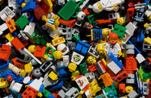 Lego minifigures and pieces of Lego lie in a pile.