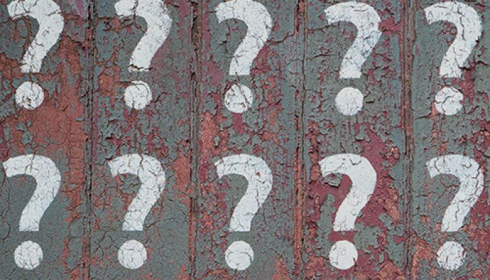 10 white question marks stenciled onto a grey-green wall. The grey-green paint is peeling revealing maroon paint underneath.