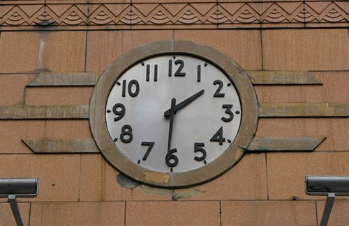 A photo of an art deco clock showing the time as 1:31. The clock features a white face with large black numbers and hour and minute hands.