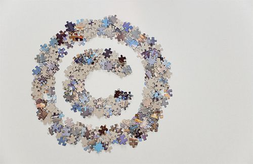 Loose puzzle pieces arranged to create a copyright symbol. The puzzle pieces are on a white background in landscape mode and with plenty of white space on the right side.