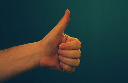 A mans' forearm and hand is visible, with his hand positioned in a thumbs up gesture.