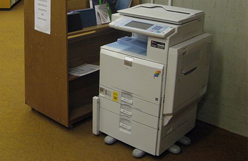 A photocopier sits alongside a book Loughborugh University Library. returns cart at the
