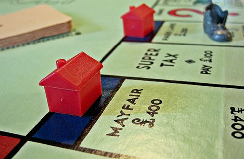 Part of a Monopoly board showing Mayfair and Park Lane with a red hotel on each.